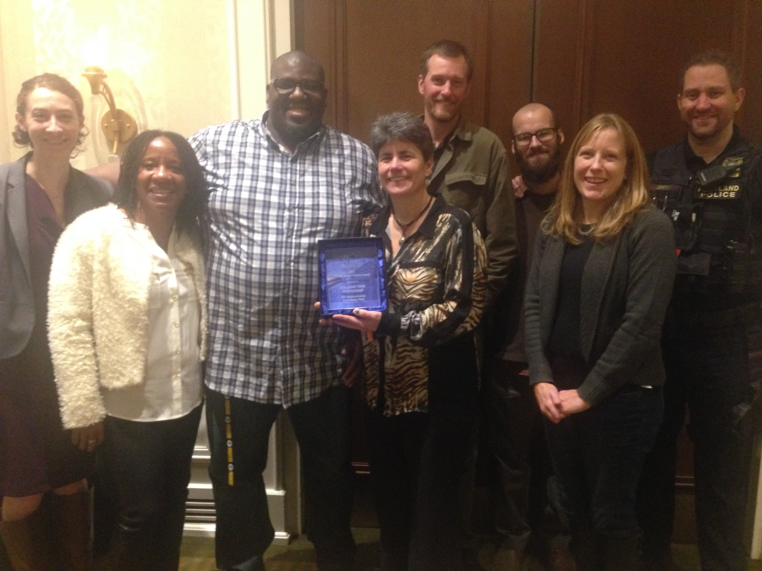 Representatives of the Holladay Park Partnership accept their award from the Oregon Recreation & Park Association. From left: Vivian Godsey (D.A., formerly assigned to the Lloyd District), Mary Tompkins, Anthony Williams (Park Ranger for Holladay Park), Sue Glenn (Parks and Recreation), Mike Grosso (Parks and Recreation), Jordan Rhodes (Event Assistant for Holladay Park), Alicia Hammock (Parks and Recreation) and Portland Police Officer Ryan Lewton.