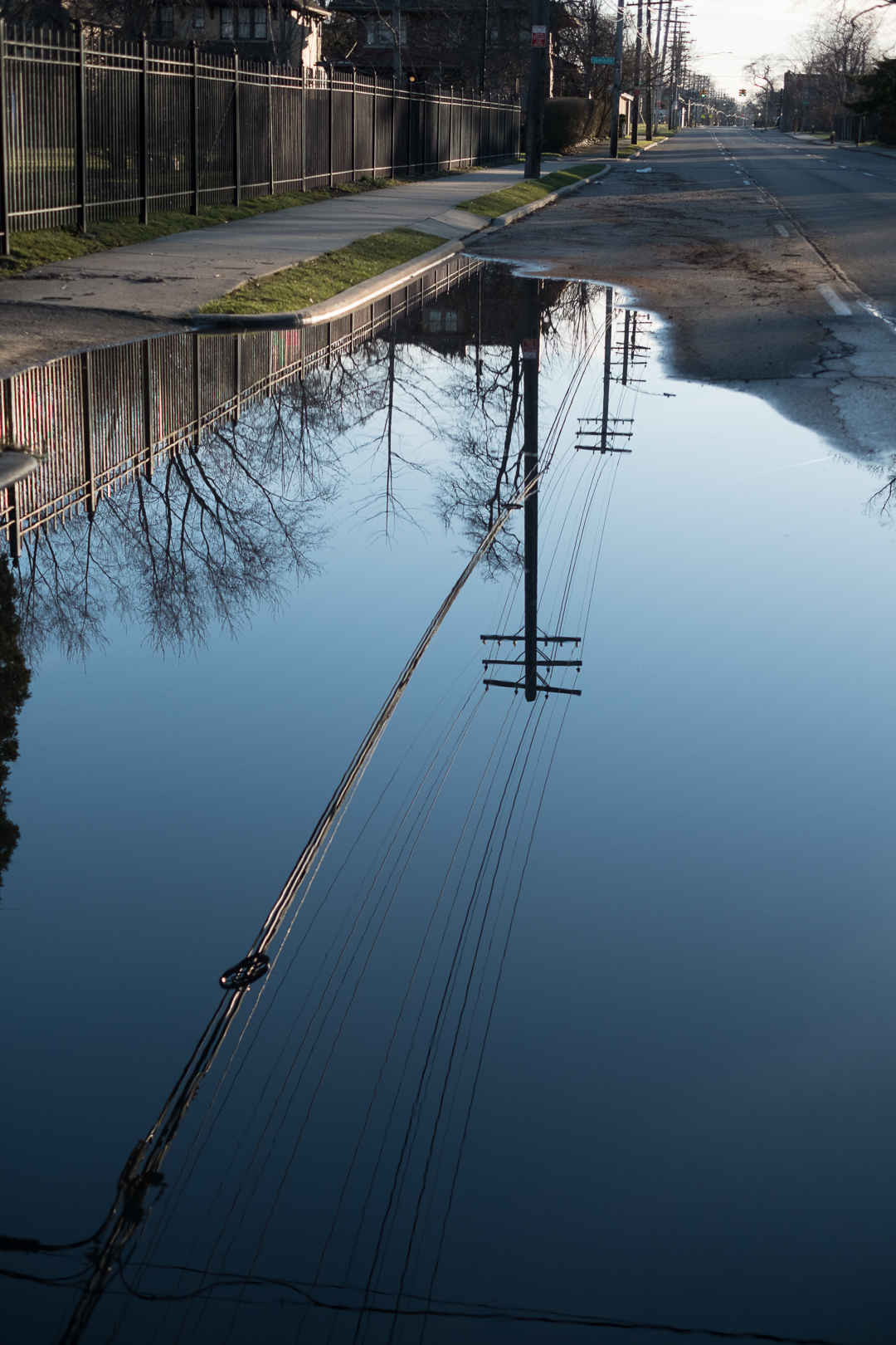 A flooded street reflect a series of power lines.