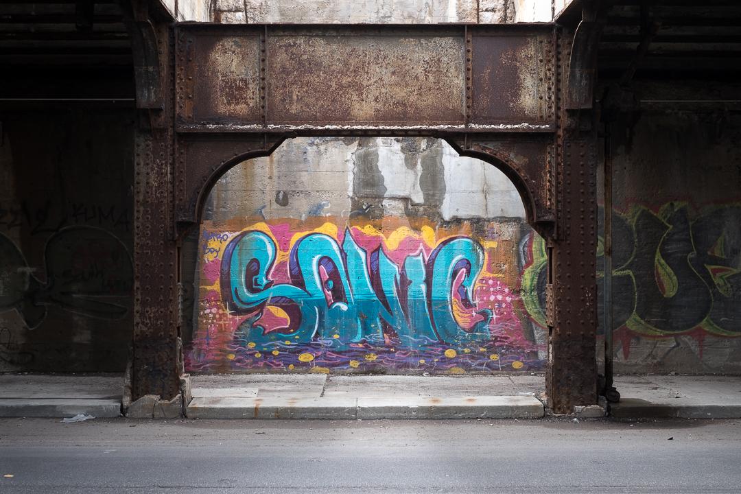 Street art being framed under an unused viaduct in Detroit's Cork Town neighborhood.
