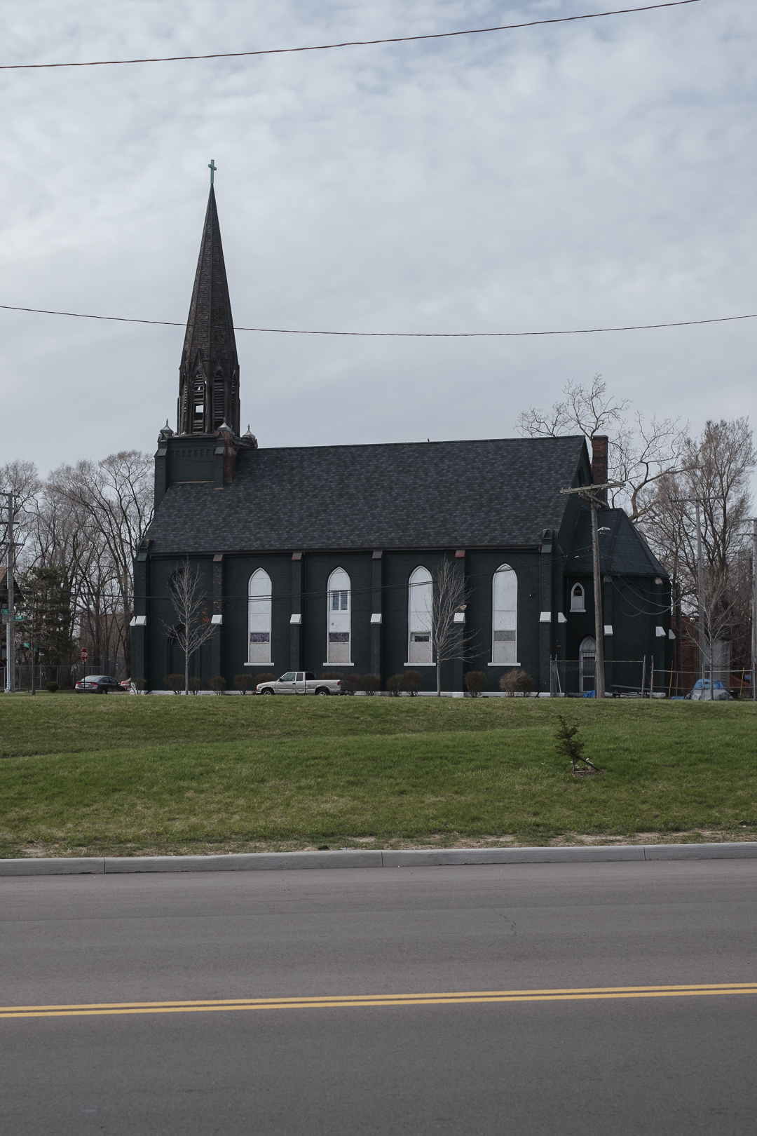 An old green traditional church building with large steeple.