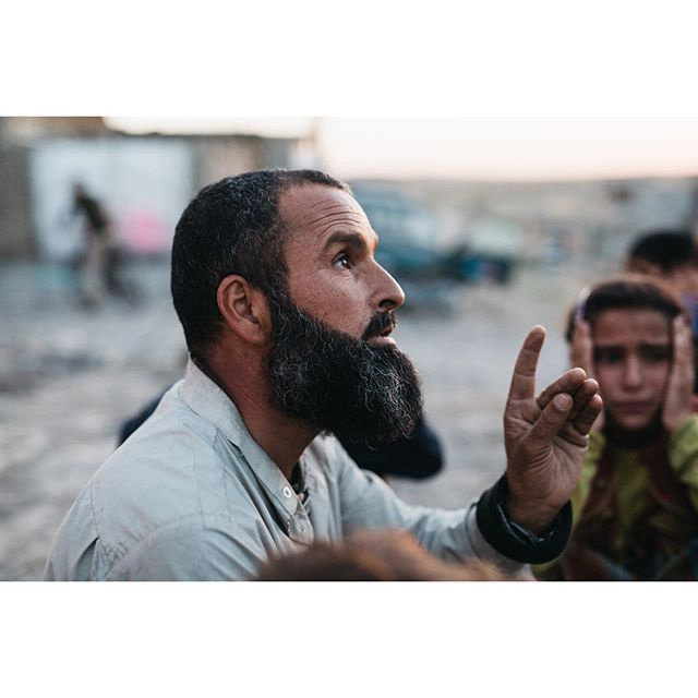 After fleeing from being held captive and used as bullet shields, a man explains the conditions under which he and his family lived, in the background his young daughter weeps Iraq, West Mosul 2017