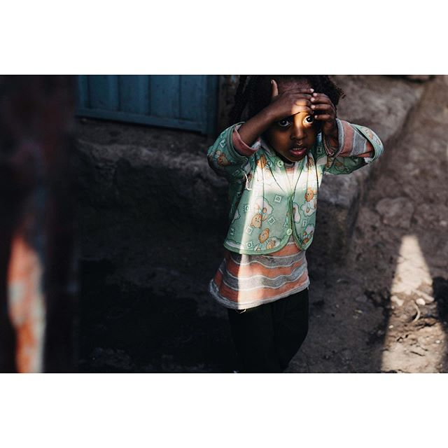 An Ethiopian child is startled as she comes around a corner in the streets of Addis Addis Ababa, Ethiopia 2015