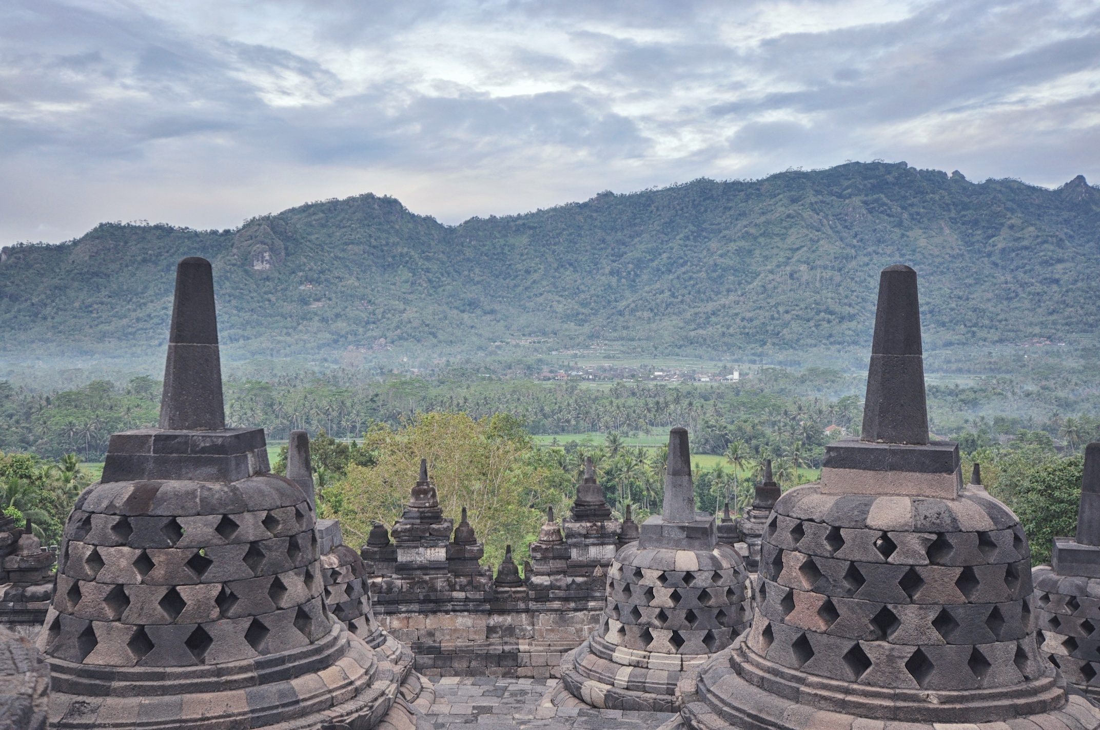 Standing at the top of Borobudur temple looking down, with Menoreh Hills in the background | © Chavelli Tsui www.chavelli.com