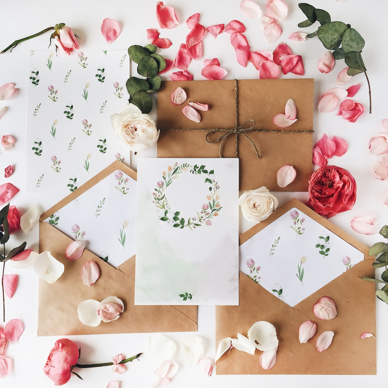 Workspace. Wedding invitation cards, craft envelopes, pink and red roses and green leaves on white background. Overhead view