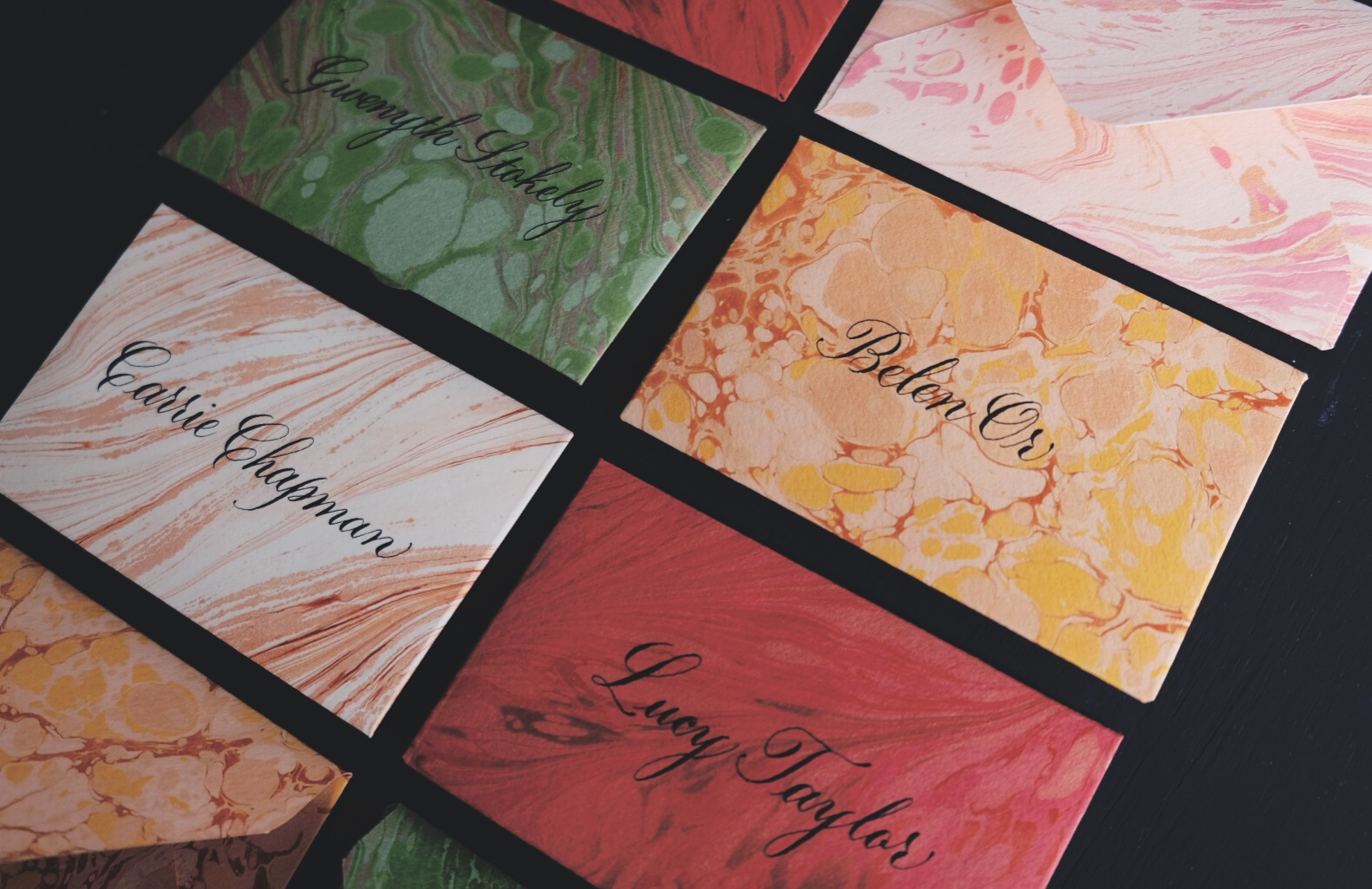 Custom marbled envelopes as escort cards with classic copperplate script calligraphy // by Chavelli www.chavelli.com