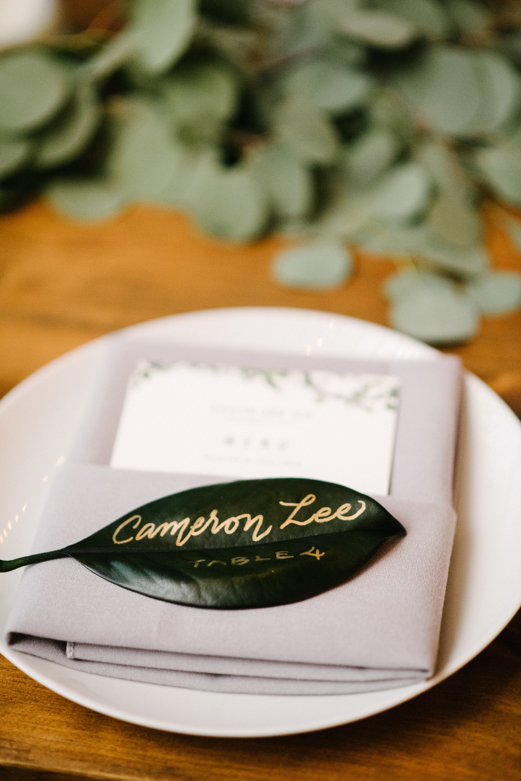 Gold calligraphy on magnolia leaf place cards   by www.chavelli.com