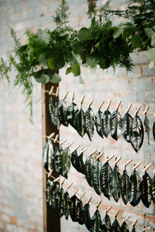 Wedding ideas: Magnolia leaf escort card display with gold calligraphy   by www.chavelli.com