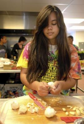 Amara Alcayde, 15 of Fairfield cuts up garlic to be used in pasta sauce for the dinner she and other interns with the Vacaville Boys and Girls Club were preparing and serving the residents of the Opportunity House. Joel Rosenbaum -- The Reporter