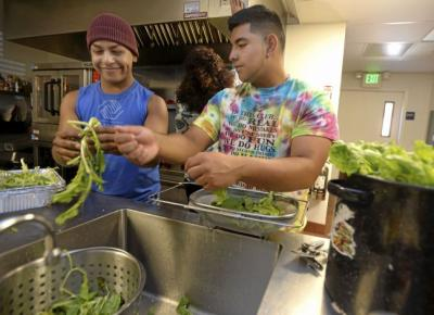 Vacaville Boys and Girls Club interns, Lio Gonzalez (left), 16 and Chris Andrade, 16 both of Vacaville wash and prepare lettuce grown in their aeroponic tower gardens for a salad that they are serving with dinner to residents of the Opportunity House on Tuesday. Joel Rosenbaum -- The Reporter