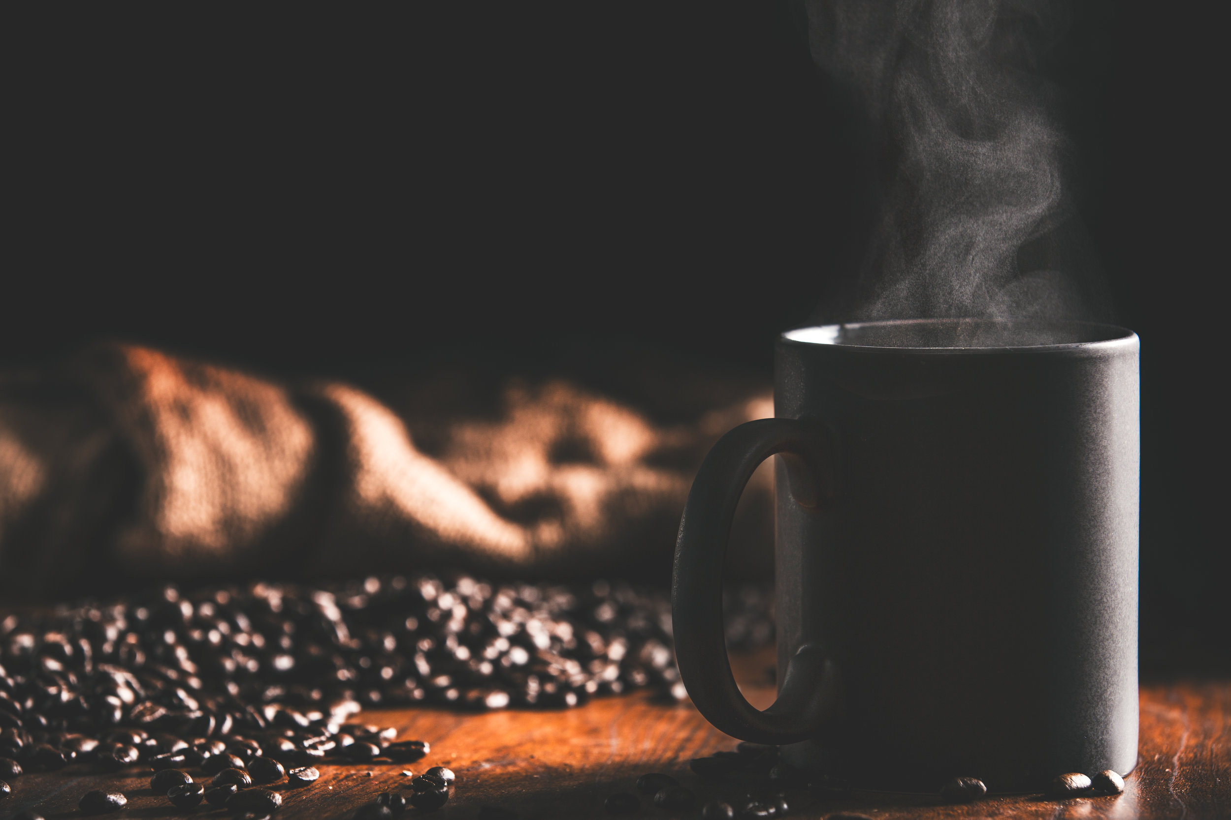 A steaming cup of fresh joe, some scattered beans pouring from a burlap sack, all on a rustic/industrial wooden table. Keep reading and watch the tutorial to see how I achieved this dramatic shot...