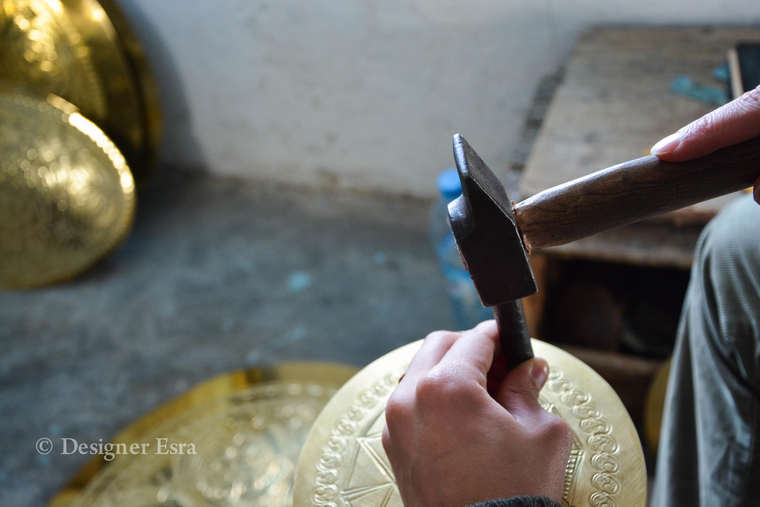 Hamza El Fasiki working on brass