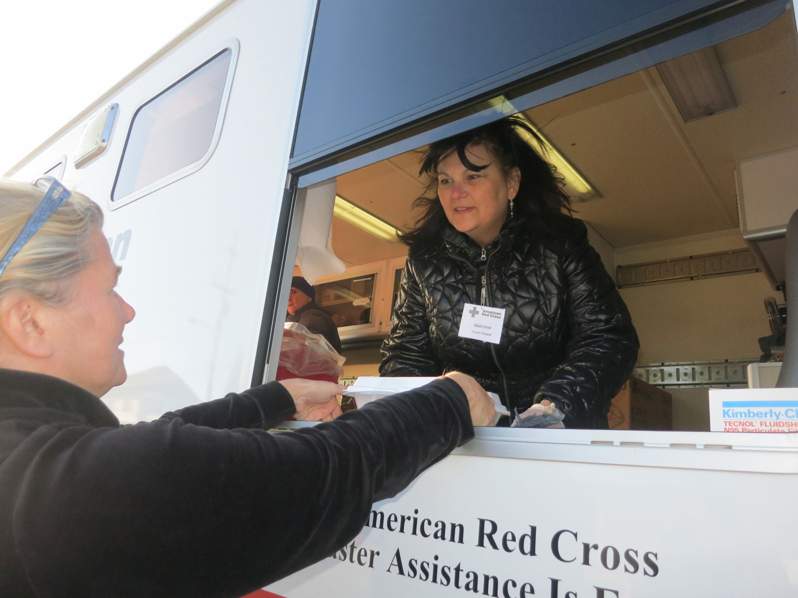 Susan Kowal serving hot turkey, string beans, mashed potatoes with gravy, apple sauce and a snack pack of goodies and water from the window in the side of the Red Cross truck known as an ERV (Emergency Response Vehicle). Families were even given a Thanksgiving table cloth but the best gift is sometimes just compassion or chance to talk about each situation.