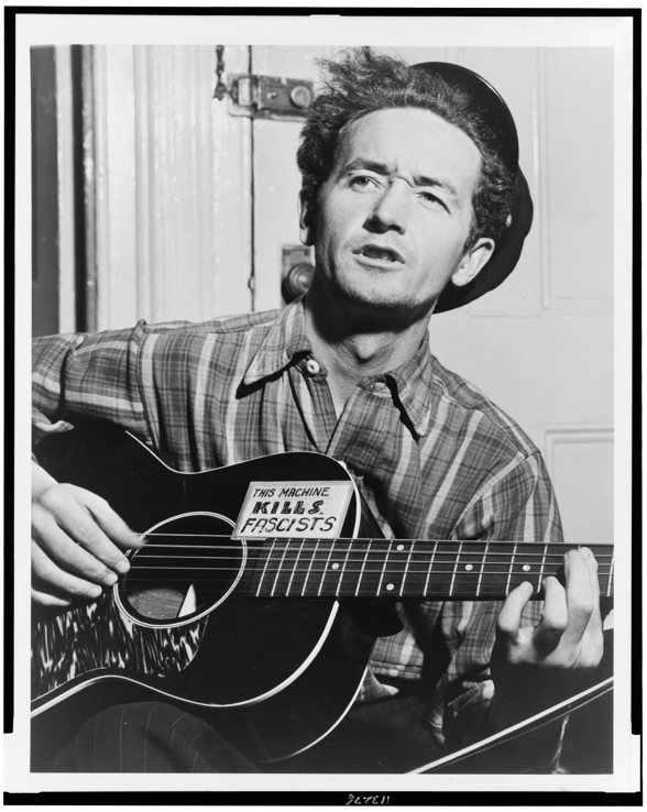 [Woody Guthrie, half-length portrait, facing slightly left, holding guitar] / World Telegram photo by Al Aumuller. | Library of Congress