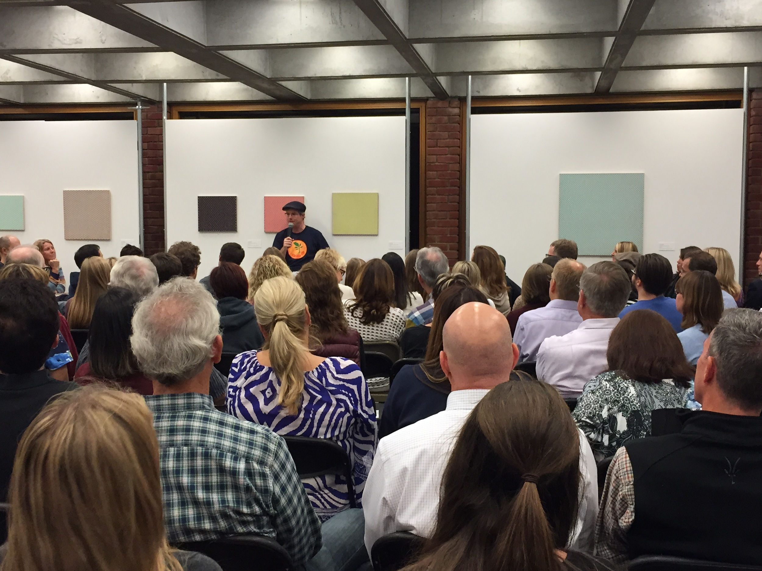 Author Andy Weir, speaking at NUMU among paintings by Stephen Beal, 2015.