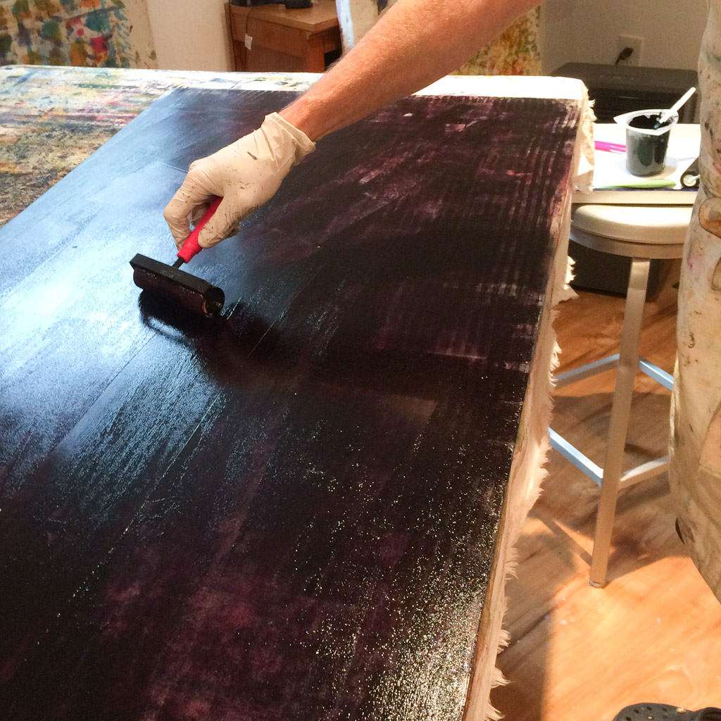 Inking a large sheet of plexiglass with thickened dye for monotype printing.