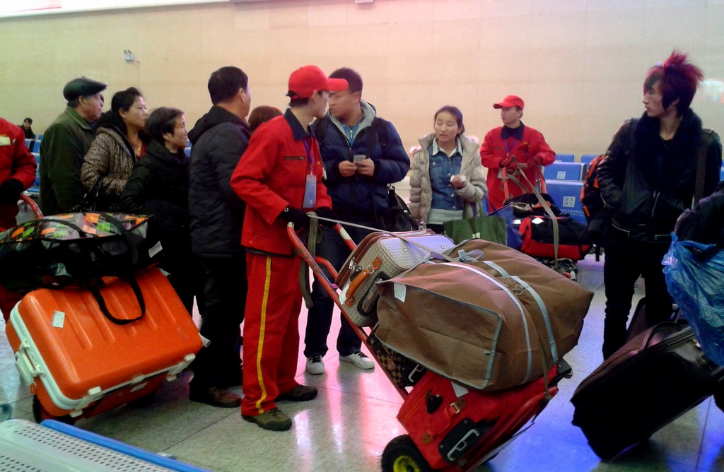 Porters manage the numerous bags, wedging them onto the cars-- no checked baggage