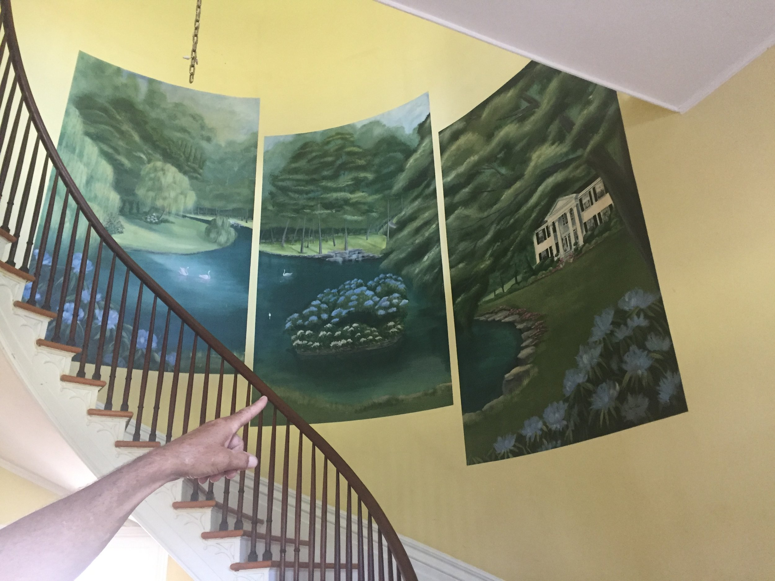 A mural of the original White Hall Farm along the wall of the spiral staircase