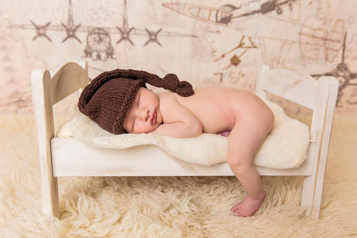Newborn sleeping on bed