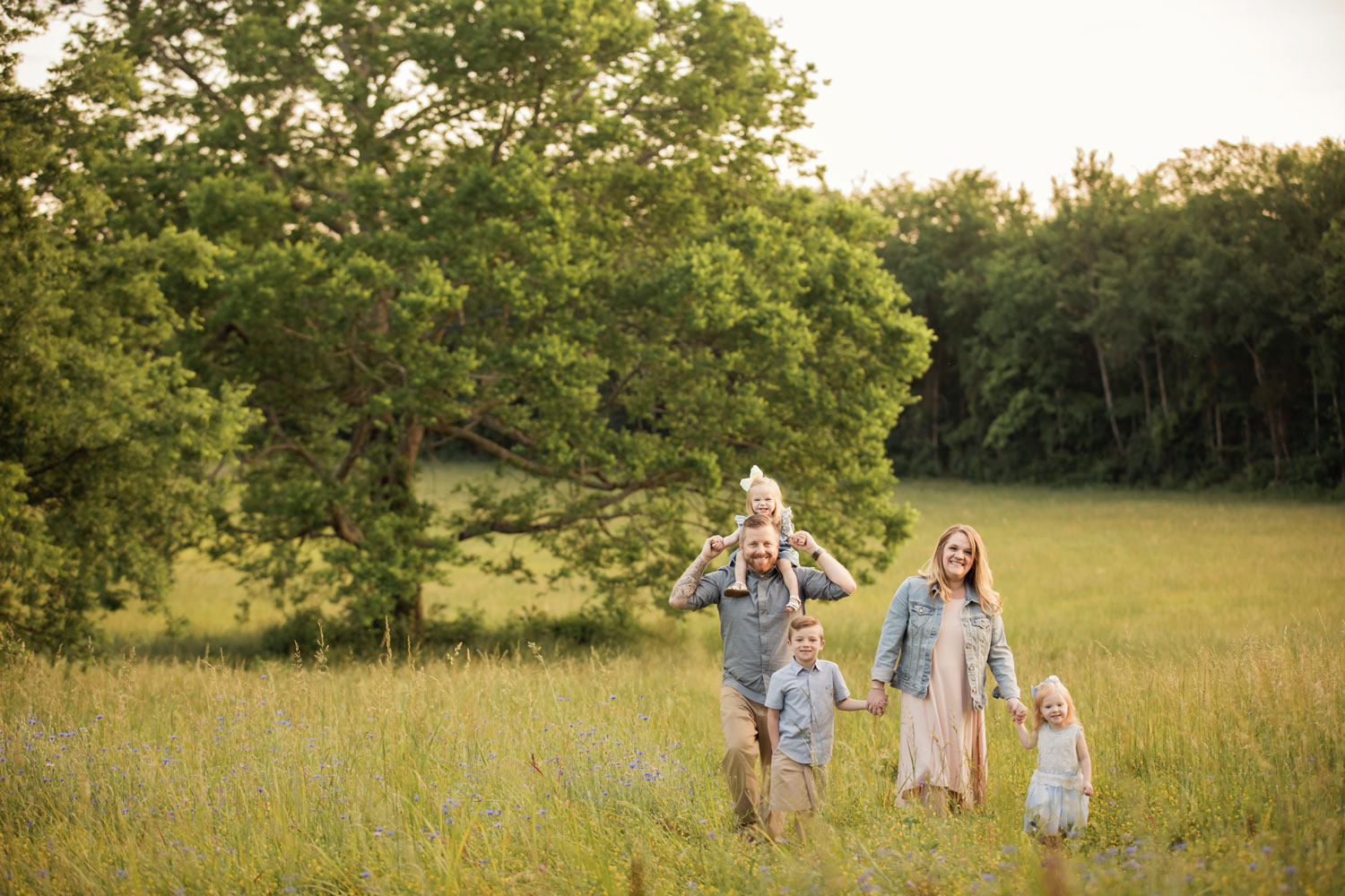 Knoxville family walks through grassy field towards photographer.