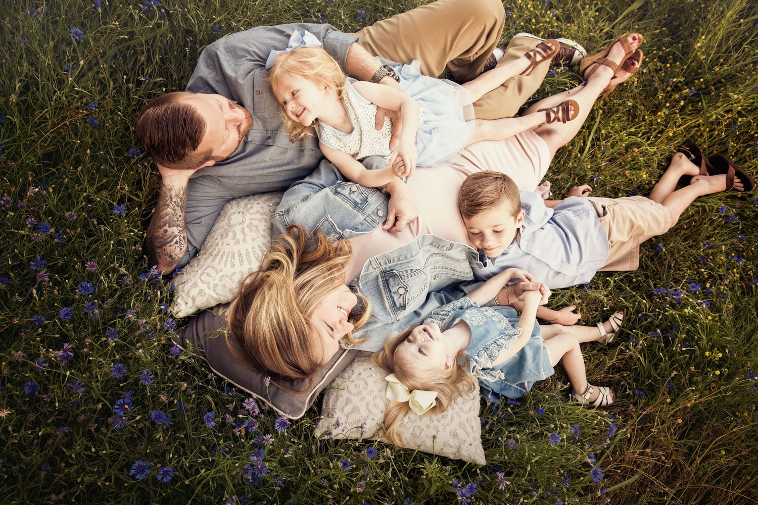 Whimsical family portrait laying in field of flowers.