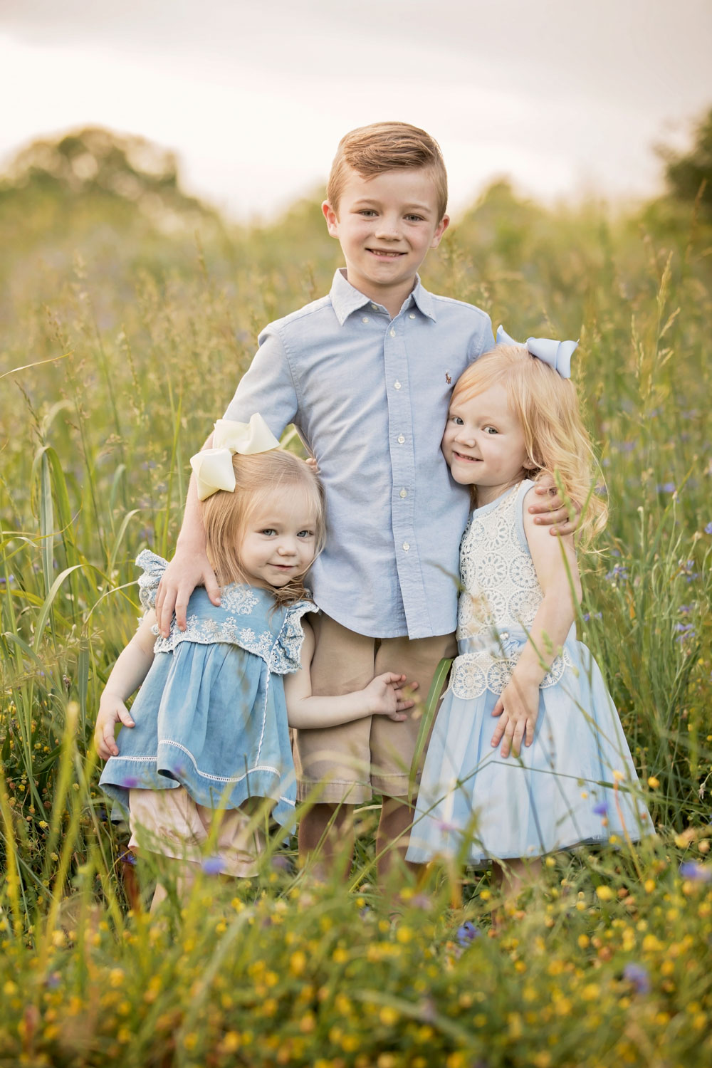 Three siblings posing in grassy field.