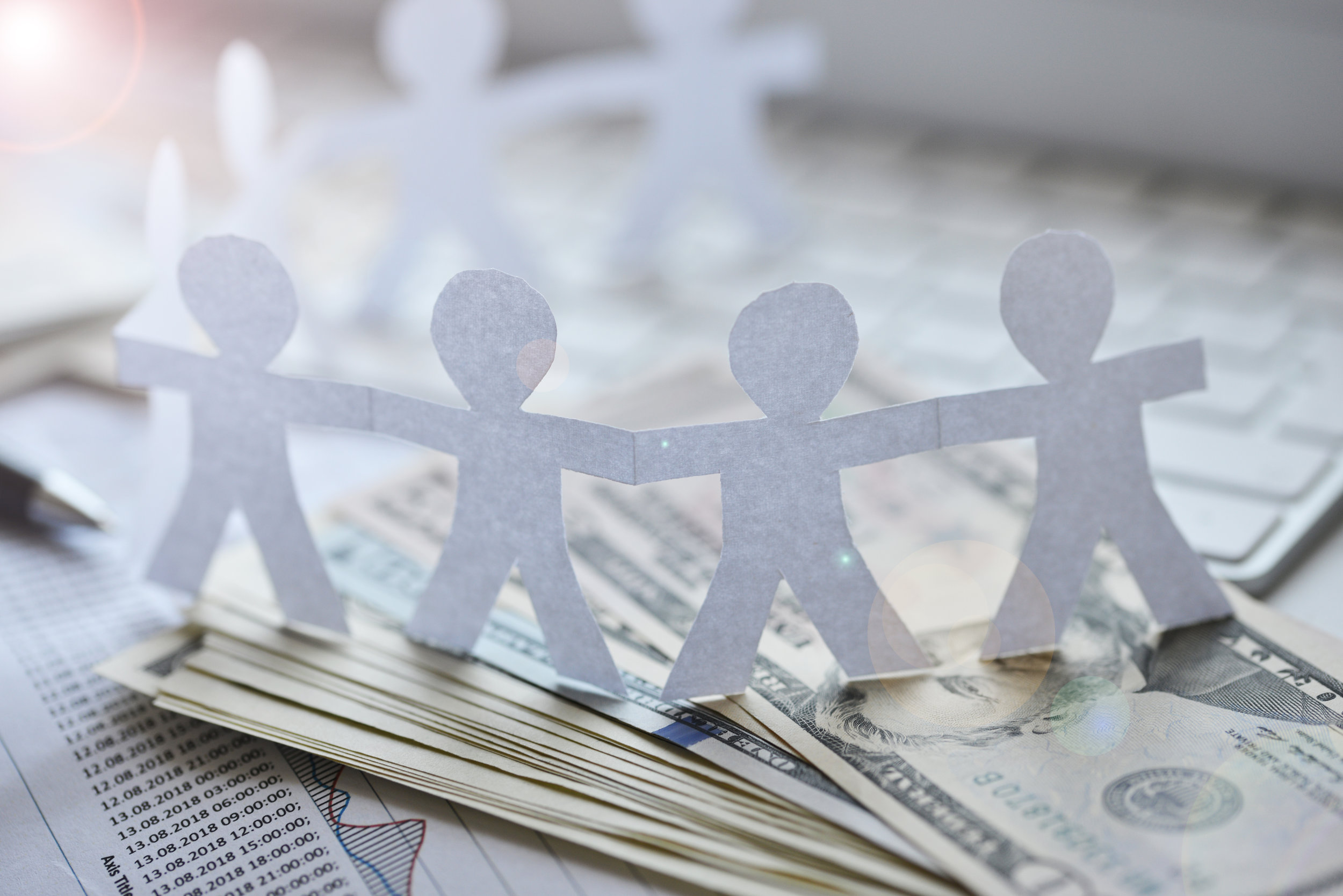 Canva - Fundraising concept with human silhouettes of paper around cash money.jpg