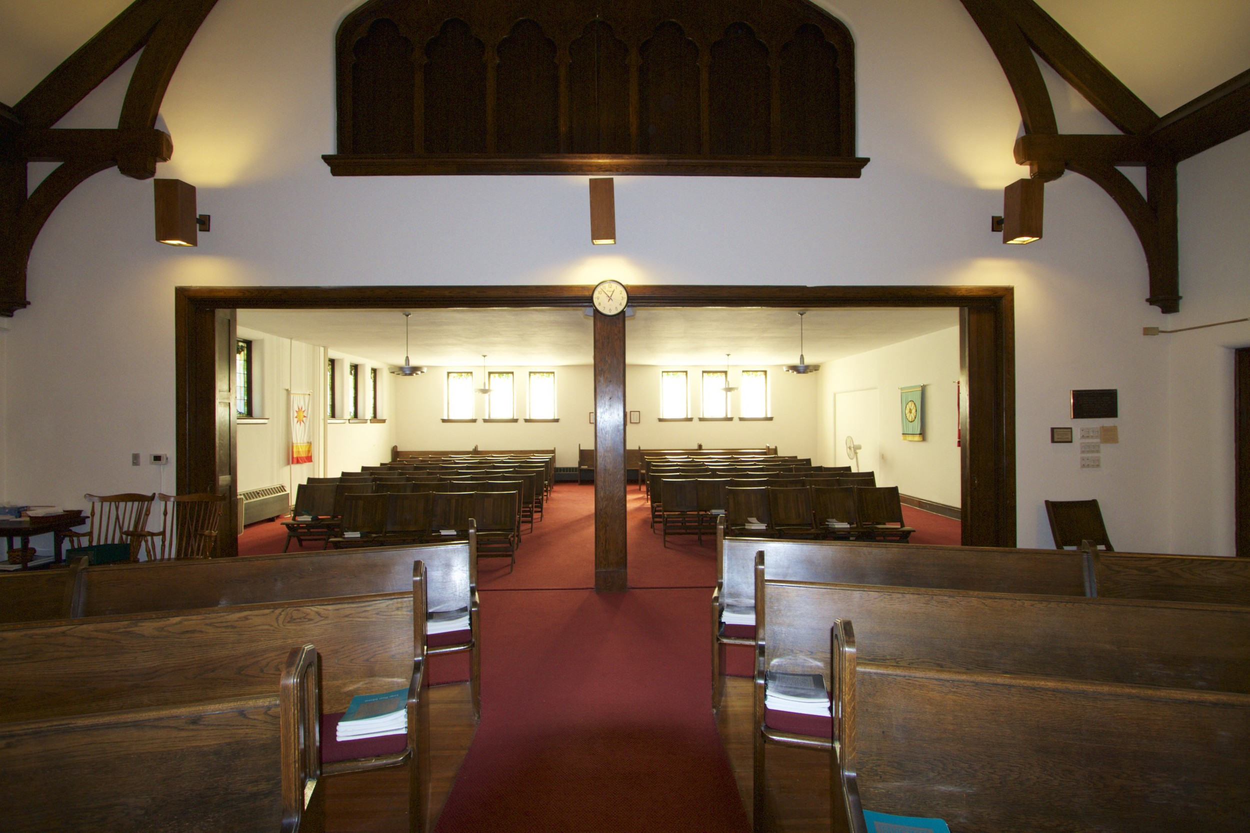 A view of the Sanctuary from the middle of the main space looking toward the back. There are nine rows of folding chairs on each side of the aisle.