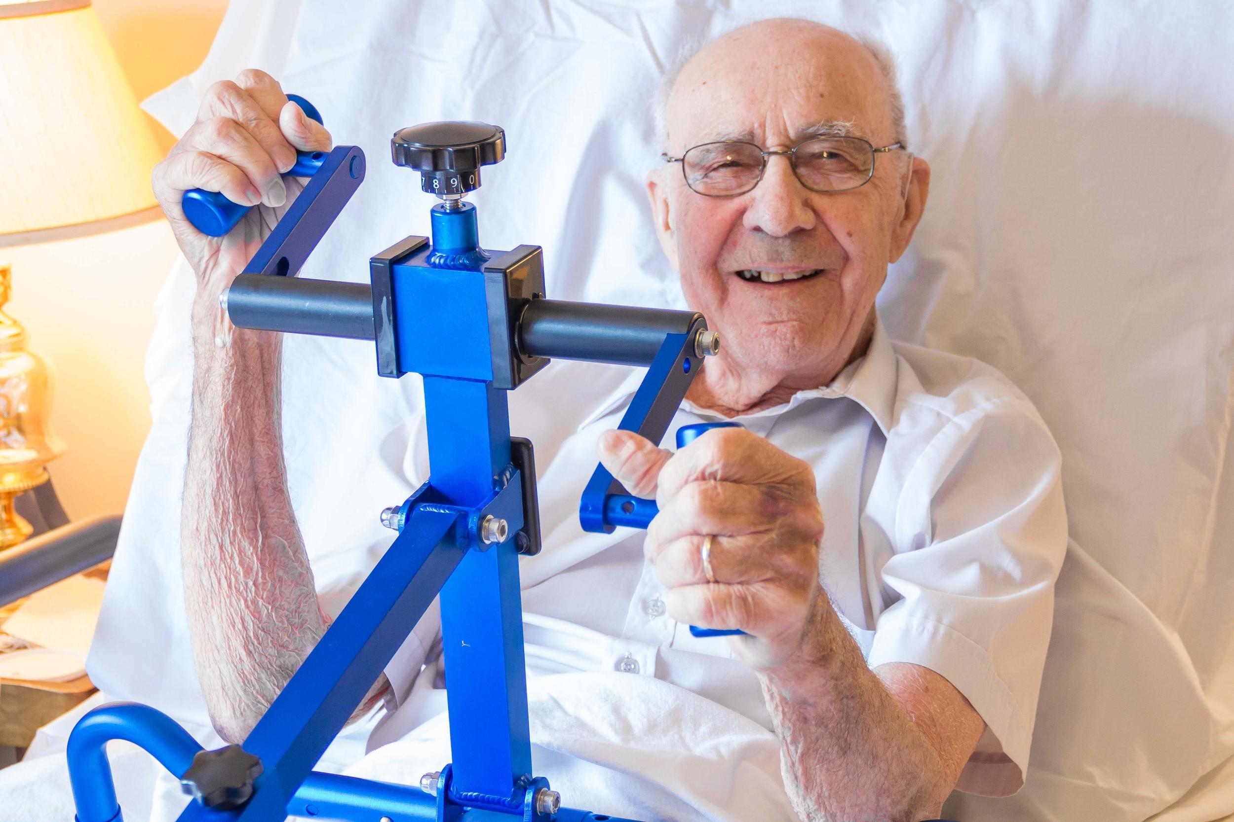 Senior man using BedBike, a portable arm ergometer