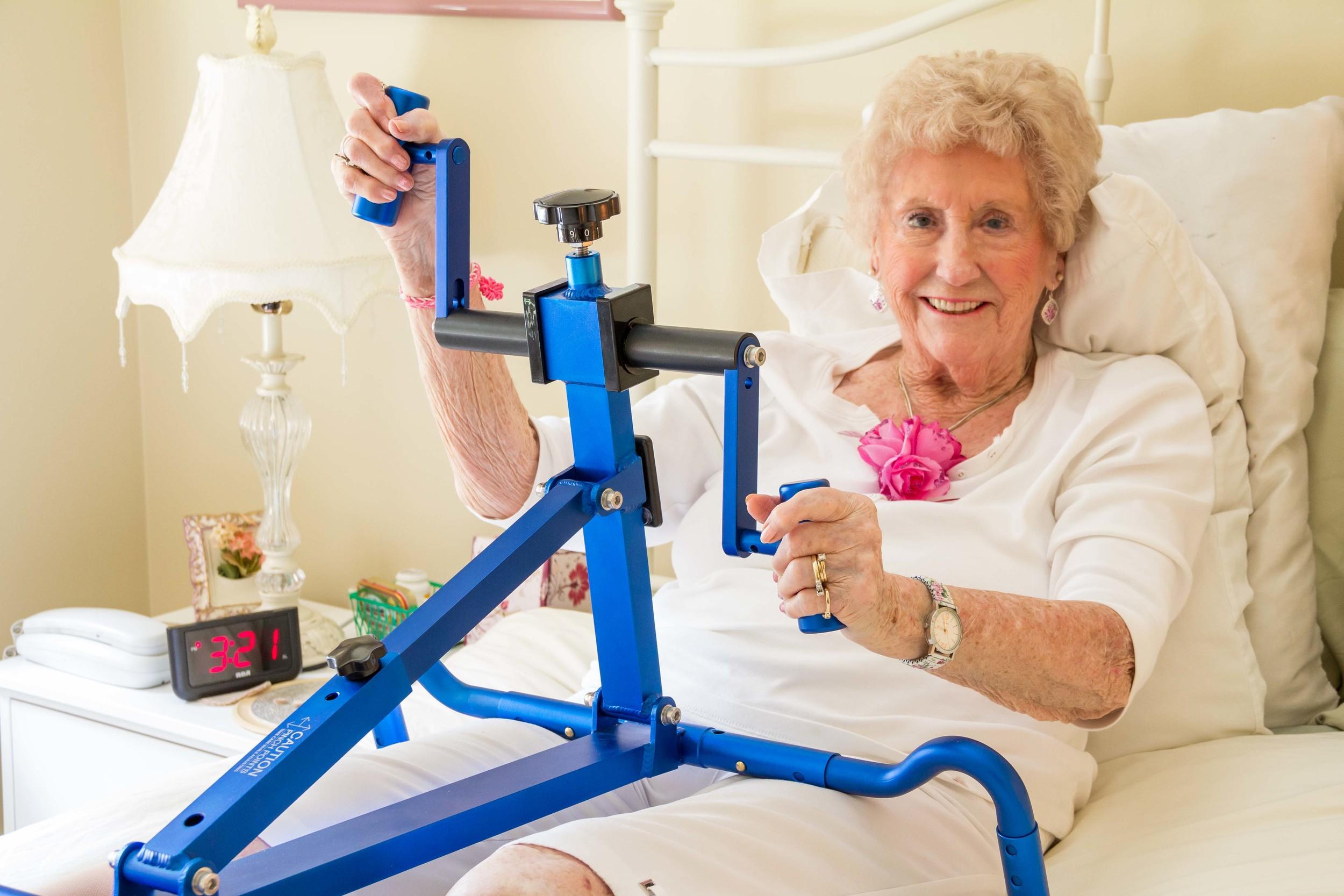 Senior woman using BedBike, a portable arm ergometer