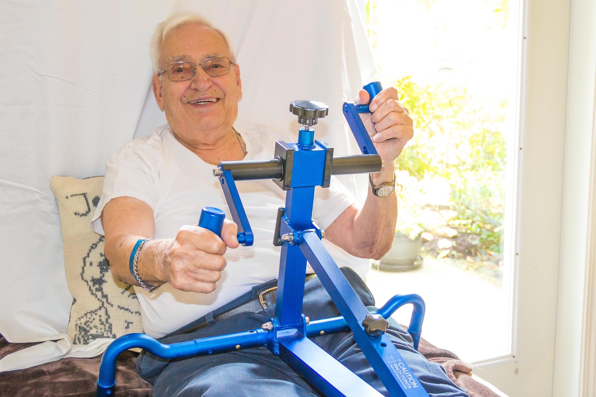 Senior using BedBike, a portable arm ergometer