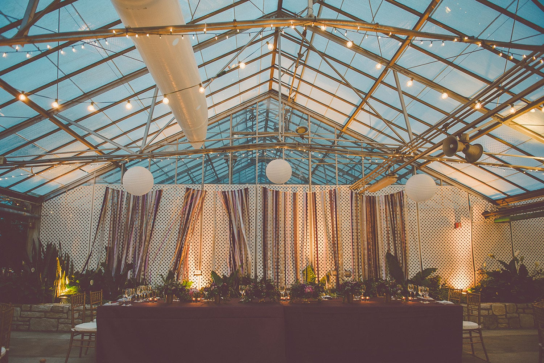 Summer wedding in Philadelphia greenhouse at the Fairmount Horticultural Center with purple ribbon wall | Wedding Plannner: Heart & Dash | Photo: Sharyn Frankel Photography | Wedding flowers: Love n' Fresh