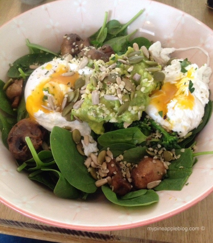 Superfood breakfast salad - kale, spinach, mushrooms, guacamole, poached eggs and seeds