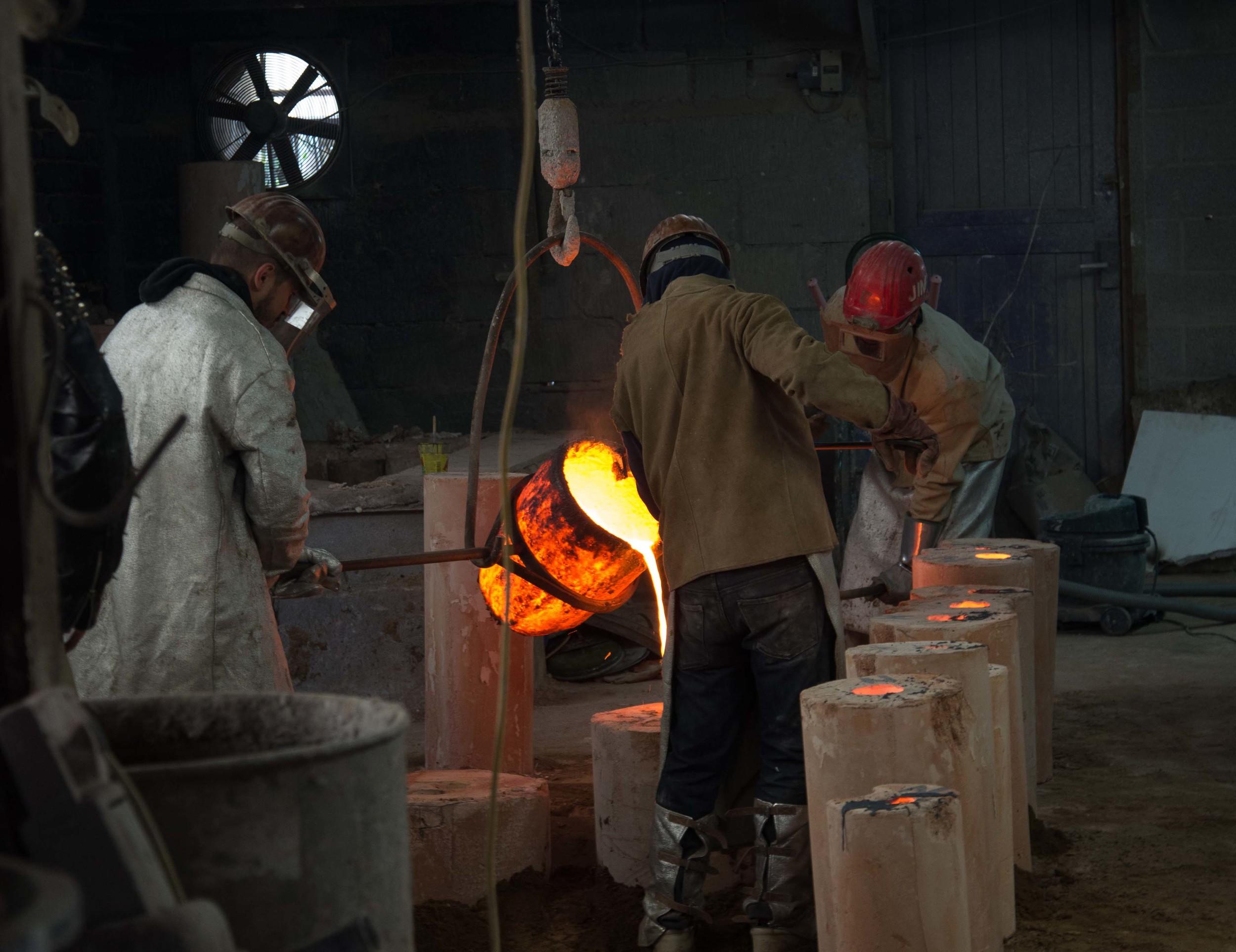 poring the liquid bronze into the mould. Critical moment...