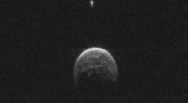 Asteroid 2004 BL86 (large object) has a small moon (top, small bright object)