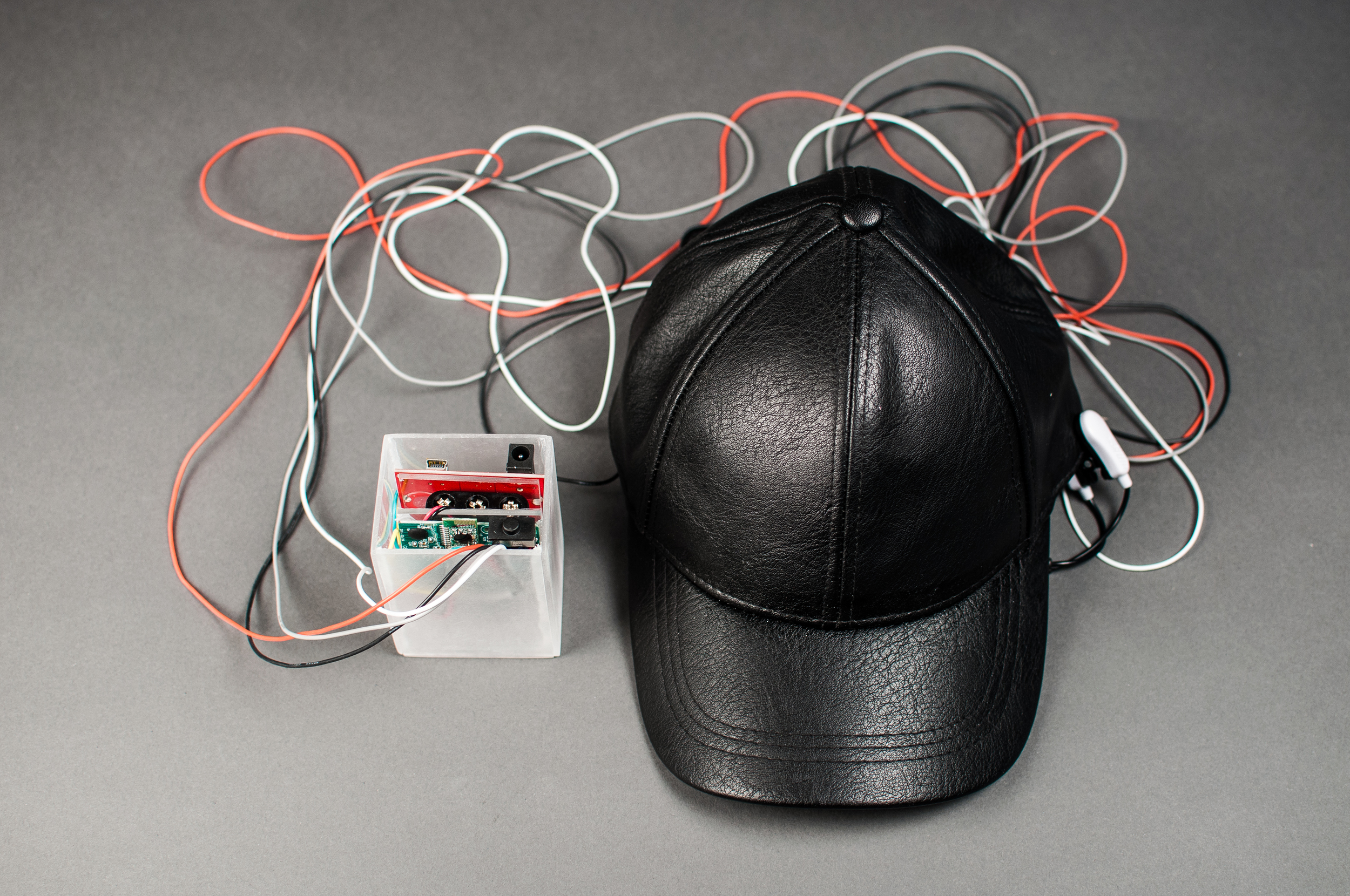 PROSTHETE's hardware: an EEG sensor is embedded in the cap; a hacked Neurosky chip sends serial data to an Arduino clone board which then parses the signal and sends it to an attached laptop.