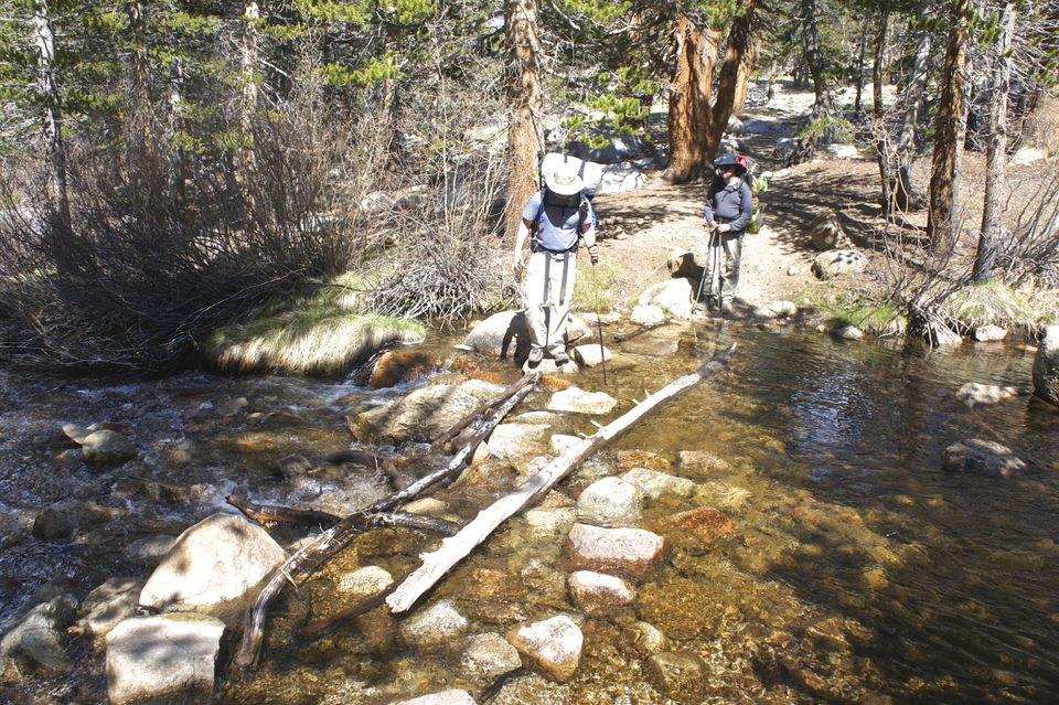 backpackers-walking-across-logs-on-a-stream