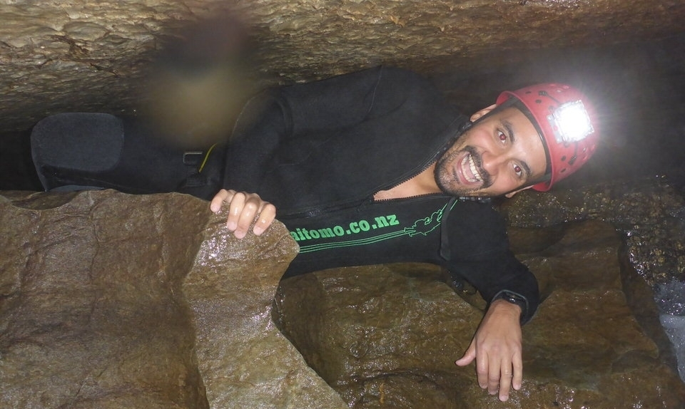 squeezing-through-cave-waitomo-new-zealand-north-island