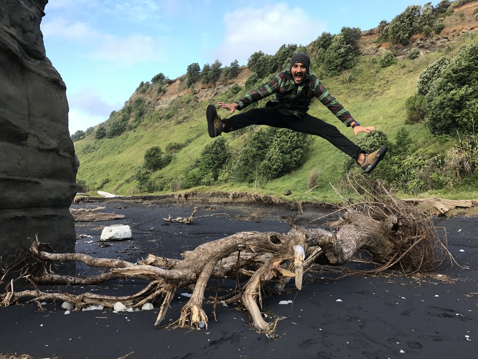 man-jump-in-air-Mokau-new-zealand-north-island