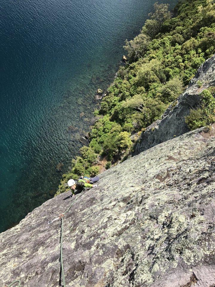 girl-rock-climbing-kawakawa-bay-lake-taupo-new-zealand