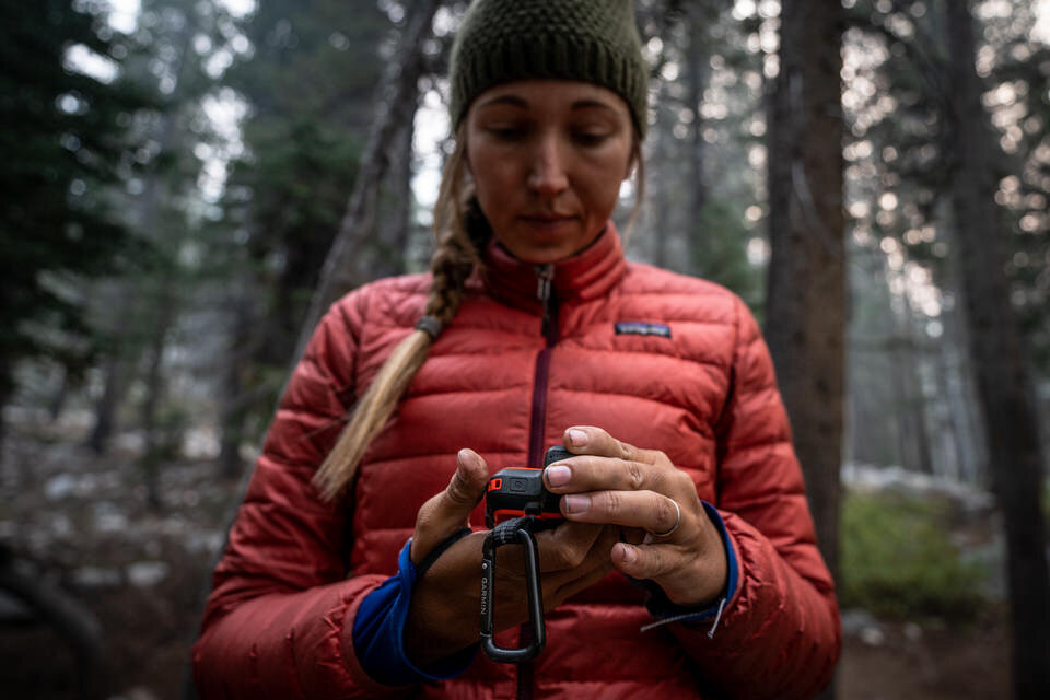 Girl who is camping using her Garmin inReach Mini.