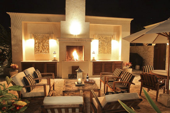 Exterior living area with fireplace and dining.