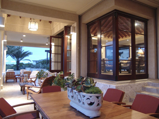 Front verandah at dusk. Dining area in foreground with two seating areas beyond.