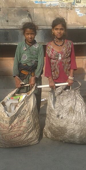 These two girls were hired to pick crops. In this photo they are holding all of their personal belongings.