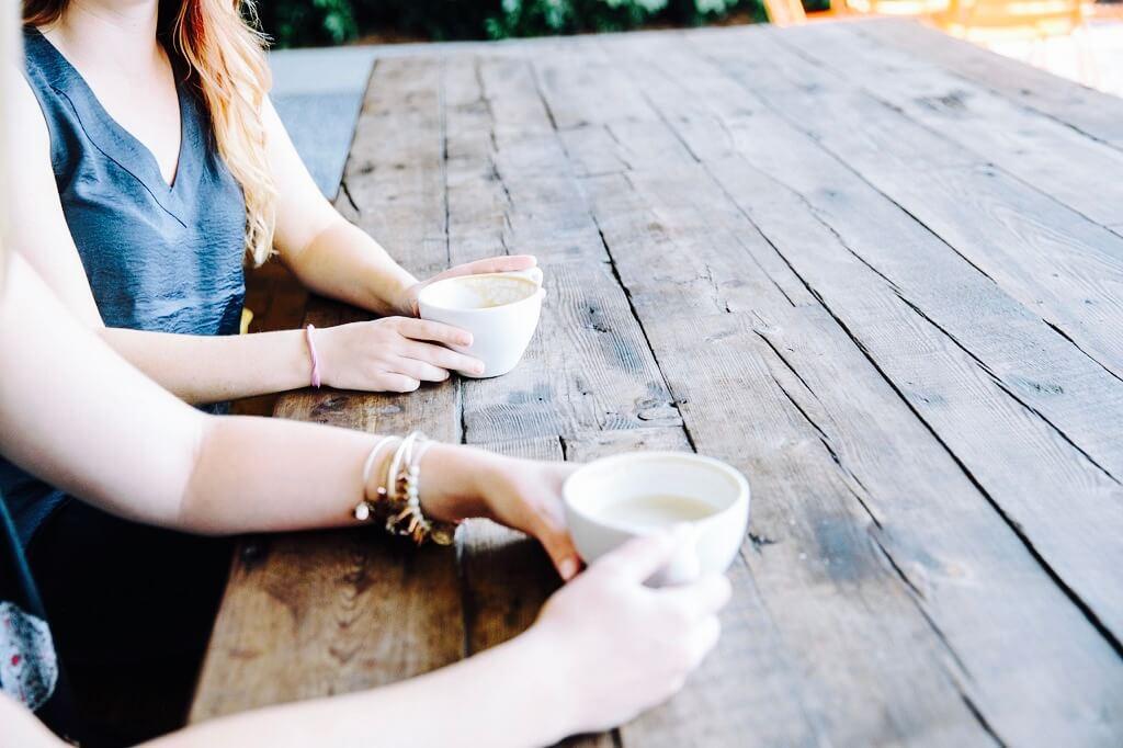 Zwei Frauen bei Besprechung mit Kaffee an Holztisch