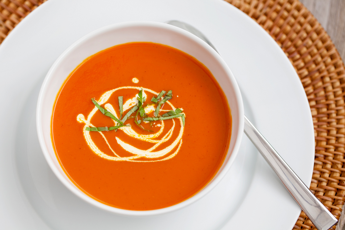Roasted Red Pepper & Tomato Soup is a vibrant red colour - serve with a drizzle of cream and some shredded fresh basil leaves for a simple but impressive garnish.
