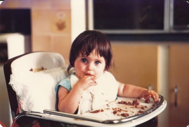 Sarah on her 1st birthday, fully immersed in her first chocolate cake experience.