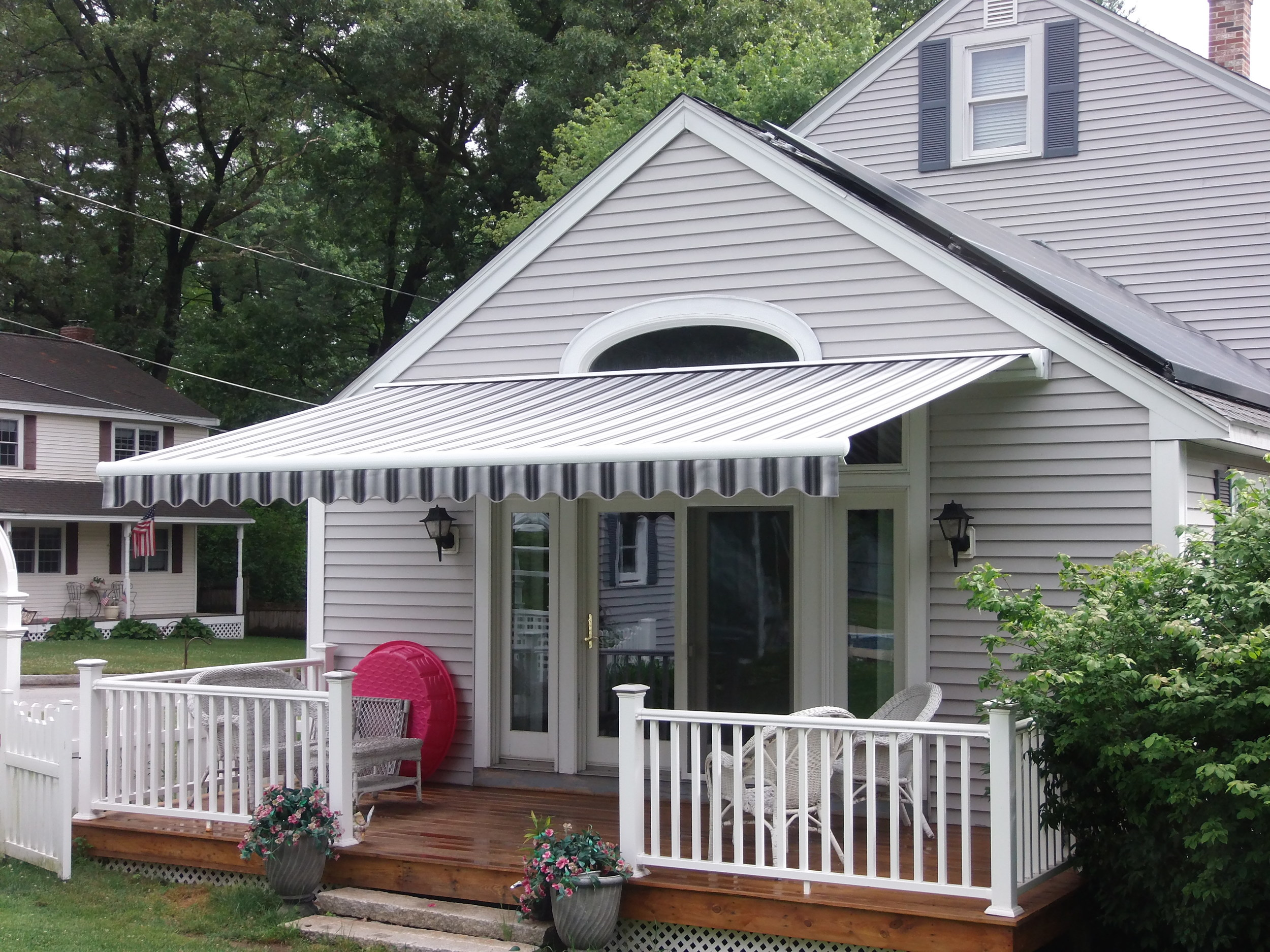 Retractable awning offering shade and style. Installed by Betterliving Sunrooms of NH in Chelmsford, MA.