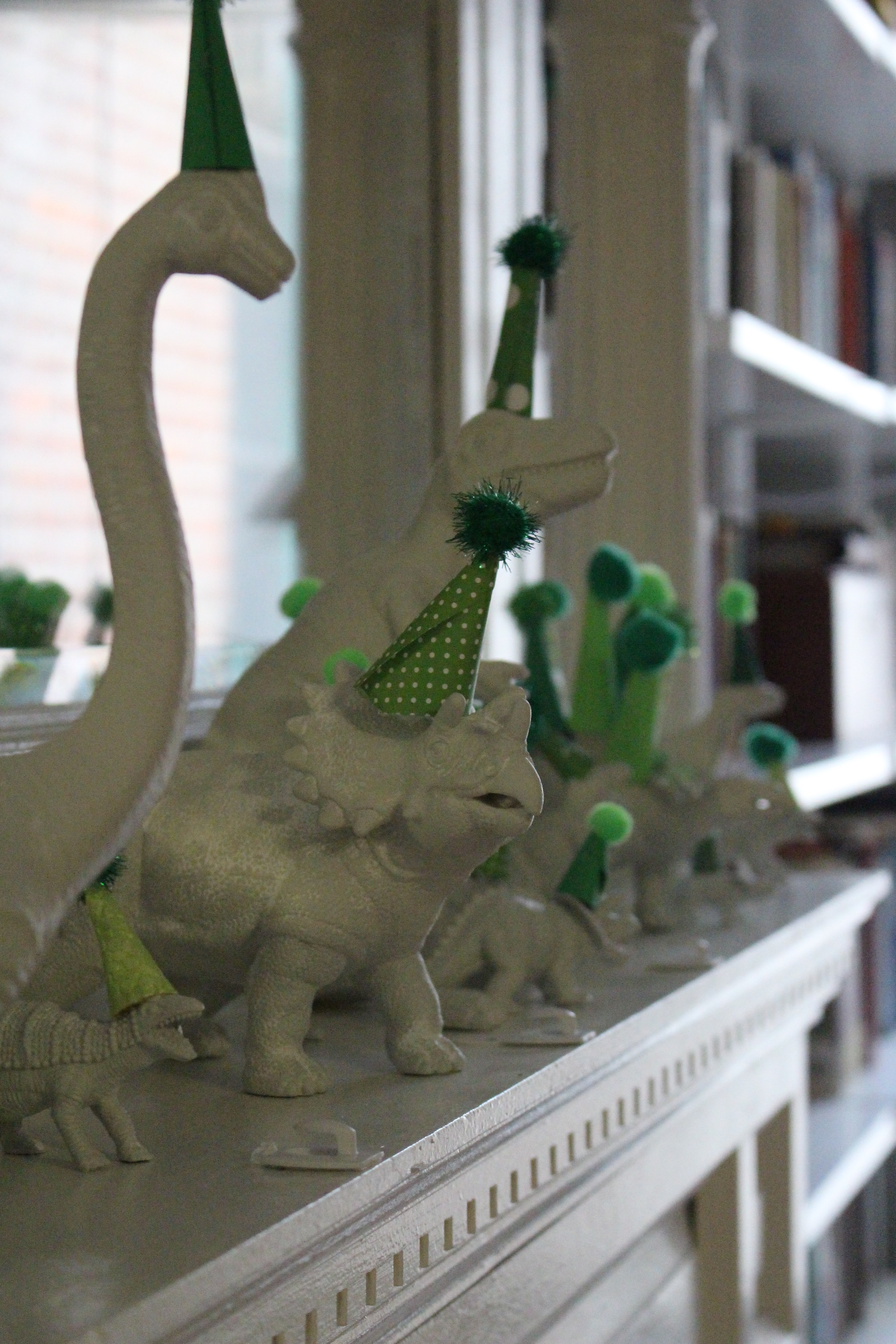 Plastic dinosaur toys from Amazon; spray-painted white; hot-glued on tiny party hats made from paper and poms from Michaels. #Moderdino #dinosaurs #firstbirthday #dinobirthdayparty #kidsbirthday #meandthemoose