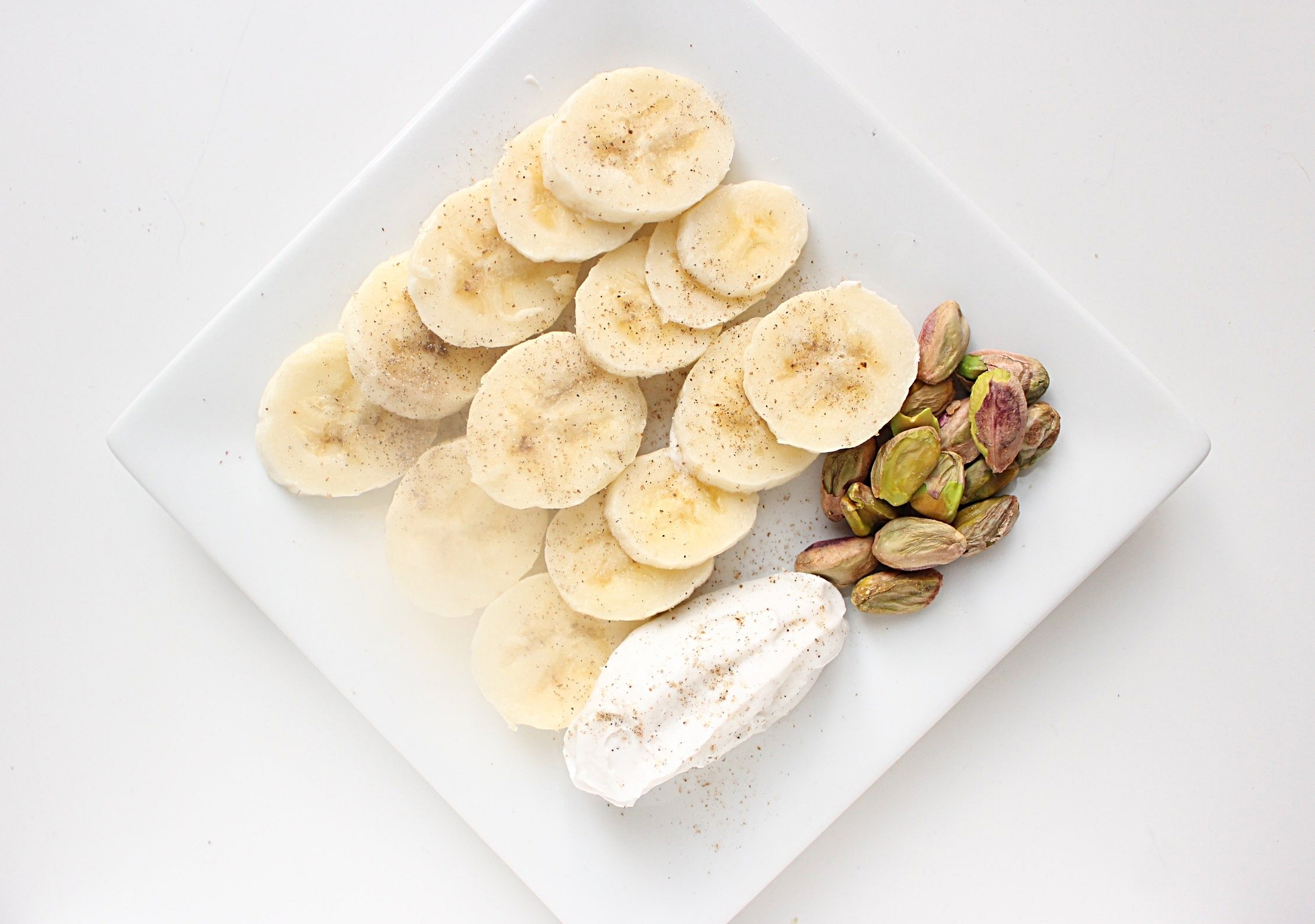 Bananas with cardamom and pistachios | Me & The Moose. Dress up your fruit with some nuts and coconut cream for more protein and fat to keep you full. #meandthemoose #whole30 #whole30recipes #bananas #snacks #snackrecipes #coconutcream #pistachios