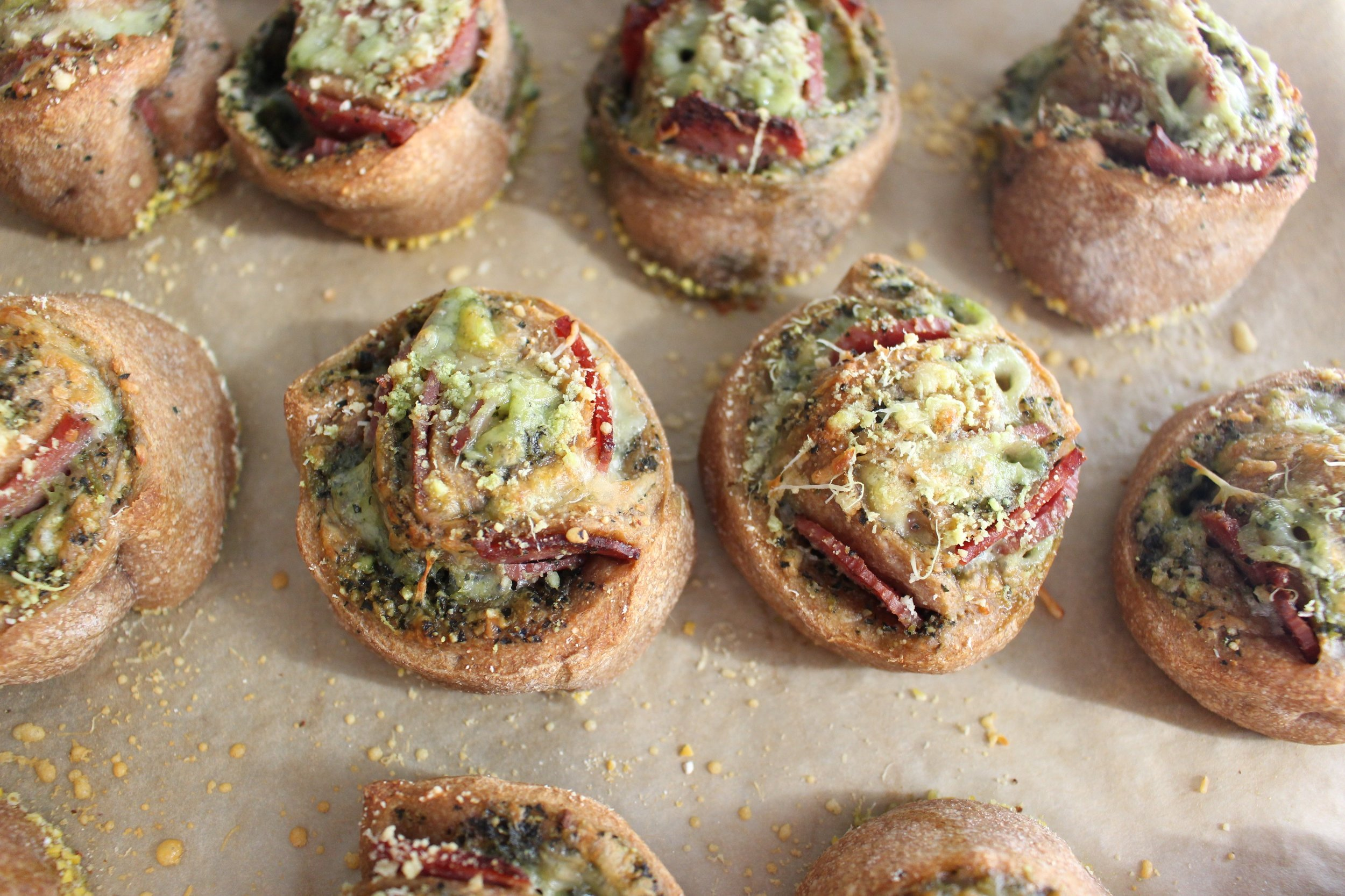 Healthy-ish pizza rolls | Me & The Moose. Whole wheat pizza crust, kale pesto, and turkey salami make these lunchbox friendly pizza rolls (just swap the walnuts in the kale pesto for sunflower or pumpkin seeds or leave them out entirely) a healthier pizza option. #meandthemoose #pizzarolls #healthypizzarecipes #healthypizza #lunchboxideas #lunchboxrecipes #lunch #pizza